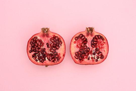 Fresh pomegranate cut in half on pink
