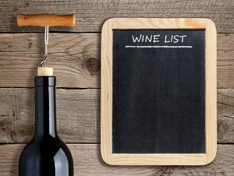 Wine list on blackboard and wine bottle on wooden background