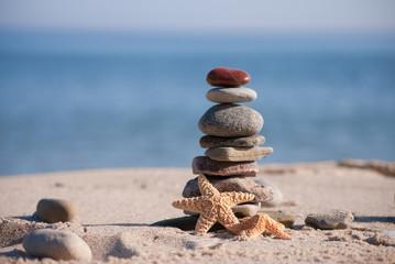 Steinstapel mit Seesternen am Meer