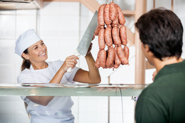 Butcher Selling Sausages To Male Customer