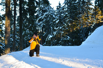 Man taking pictures with camera on sky slope in winter