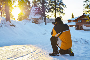 Photographer man taking pictures to the sunset in Poiana Brasov on ski slope