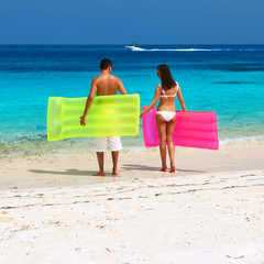 Couple with inflatable rafts on a tropical beach