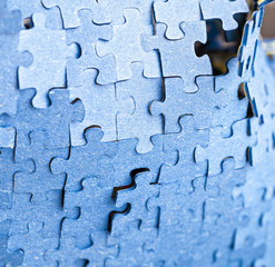 Backside of blue puzzle jigsaw in available light
