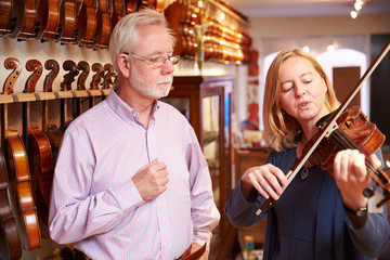 Customer Trying Out Violin In Music Store