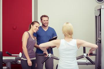 freundlicher trainer berät frauen im fitness-studio