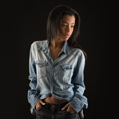 Studio portrait of brazilian woman against black background.