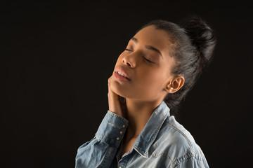 Closed eyes portrait of brazilian woman against black background