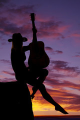 silhouette of a woman with a guitar sit leg out