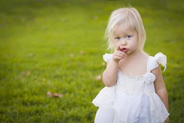 Adorable Little Girl Wearing White Dress In A Grass Field
