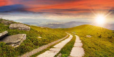 road on a hillside near mountain peak at sunset