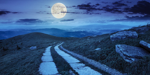 road on a hillside near mountain peak at night