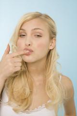 Junge Frau mit dem Finger auf den Mund, Portrait
