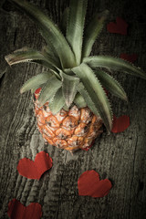 Many Valentine hearts with ananas on the old wooden table. Toned