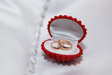 Red jewelry box with gold wedding rings on the white fabric