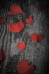 Many Valentine hearts on the old wooden table. Toned