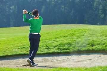 Golfer chipping the ball from sand trap, golf ball in the air.