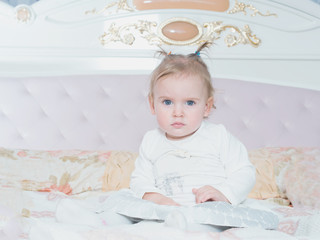 Small caucasian child girl sitting on the bed at home