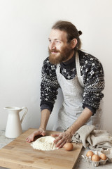 bearded stylish man with apron making dough for fresh pasta