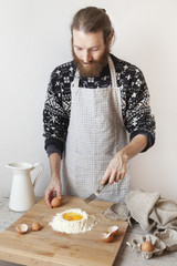 bearded stylish man with apron making dough for pasta