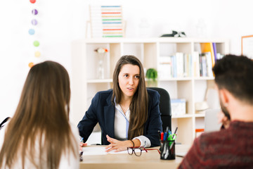 Young woman working at her desk with clients