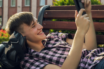 young man lying on bench in park and readindg funny e-book