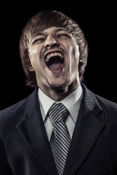 young successful businessman laughing hard over black
