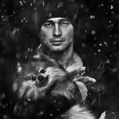Portrait of a man with a dog on a black background, snow