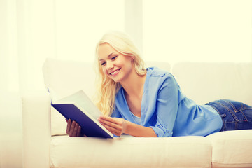 smiling woman reading book and lying on couch