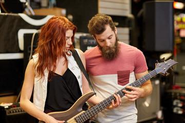 Spoed Foto op Canvas Muziekwinkel musicians playing bass guitar at music store