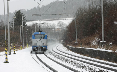 Czech train station at winter with train in a snowstorm