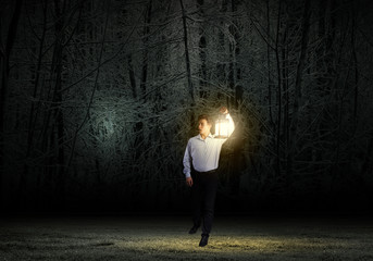 Businessman in search in darkness