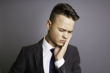 Young businessman with toothache