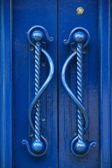 Bright blue door and ornate handles