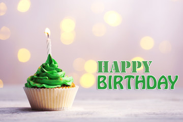 Delicious birthday cupcake on table on festive background