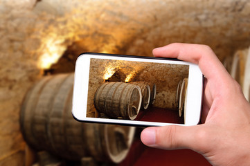 Hands taking photo old wine barrels with smartphone.