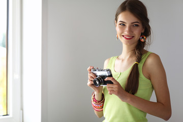 Beautiful young woman with camera standing near window