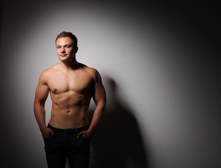 Healthy muscular young man standing on a dark background