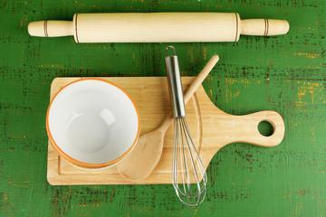 Kitchen utensils for baking on color wooden background