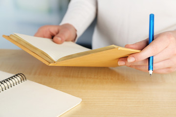Female hand with pen and diary at wooden desktop