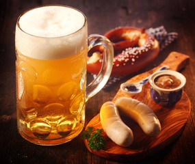 Mug of beer with German sausages and pretzels