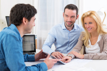 Young attractive couple signing contract on tablet