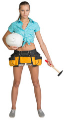 Pretty girl in tool belt holding white helmet and hammer. Full