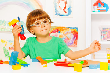 Smart boy with plastic tools in classroom