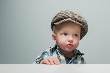 little boy in a cap looks up