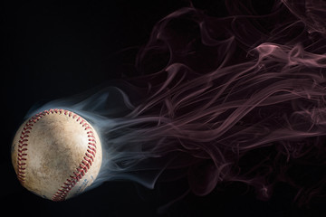 Baseball on black ground with white smoke coming off of it, which then turns to red smoke. Copy Space above the ball.