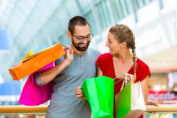 Mann und Frau in Kaufhaus mit Einkaufstüten