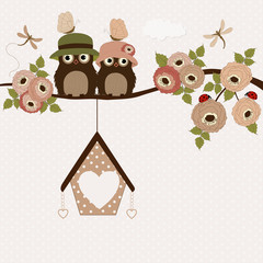 Cute owls on a branch with roses
