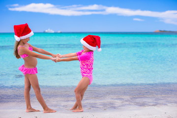 Little cute girls in Santa hats during summer vacation