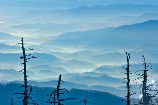 The sun highlights the mist as it climbs over the mountain peaks.